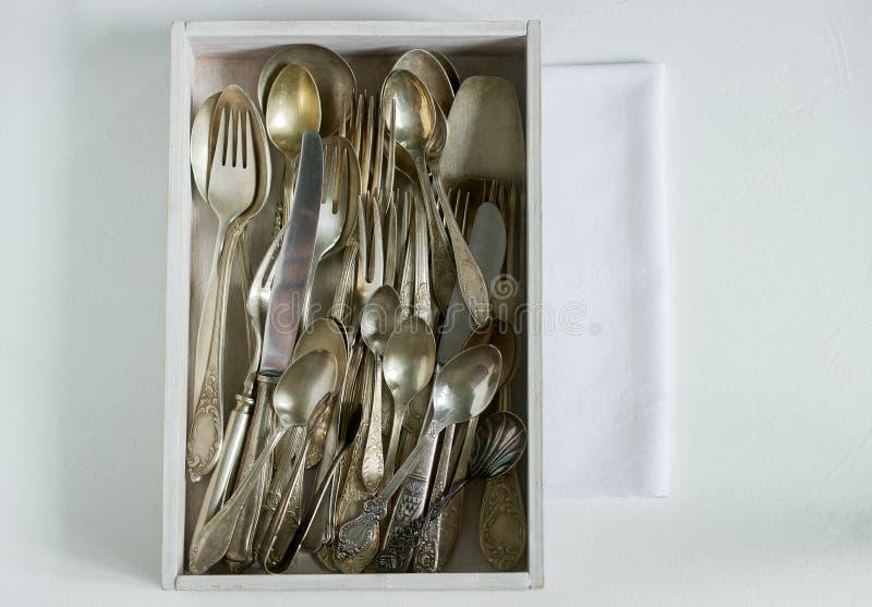 Cubiertos de plata del vintage en una caja de madera blanca en una tabla blanca Estilo rústico imagenes de archivo