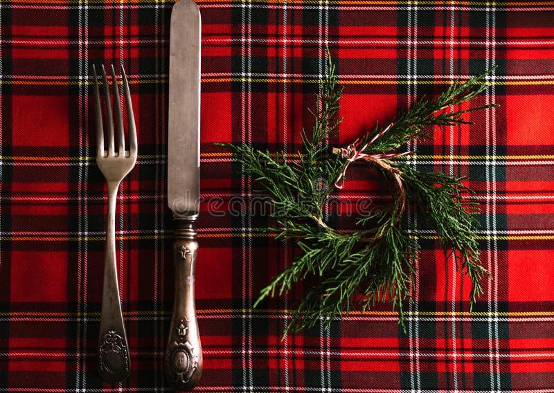Cubiertos del vintage con la pequeña guirnalda del pino en el paño a cuadros rojo, menú festivo Fondo de la Navidad o de la acció fotografía de archivo