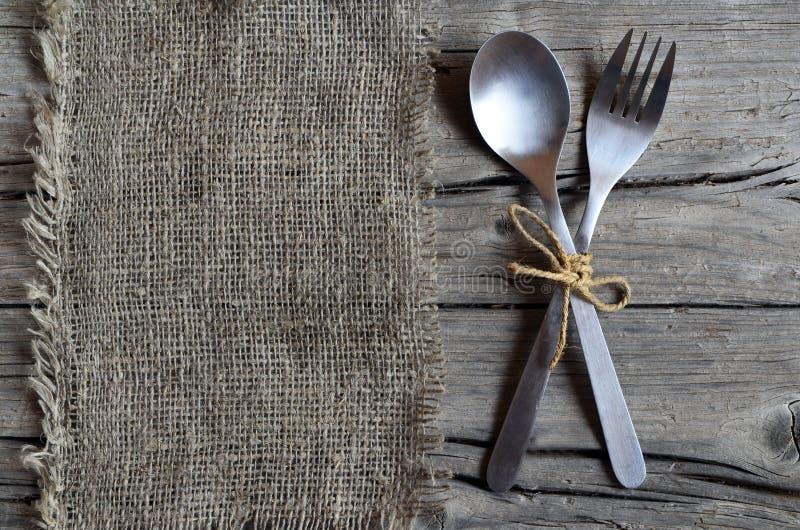 Cubiertos fijados: bifurcación y cuchara en el paño de la arpillera en la tabla de madera rústica Cubiertos en viejo fondo de mad foto de archivo libre de regalías
