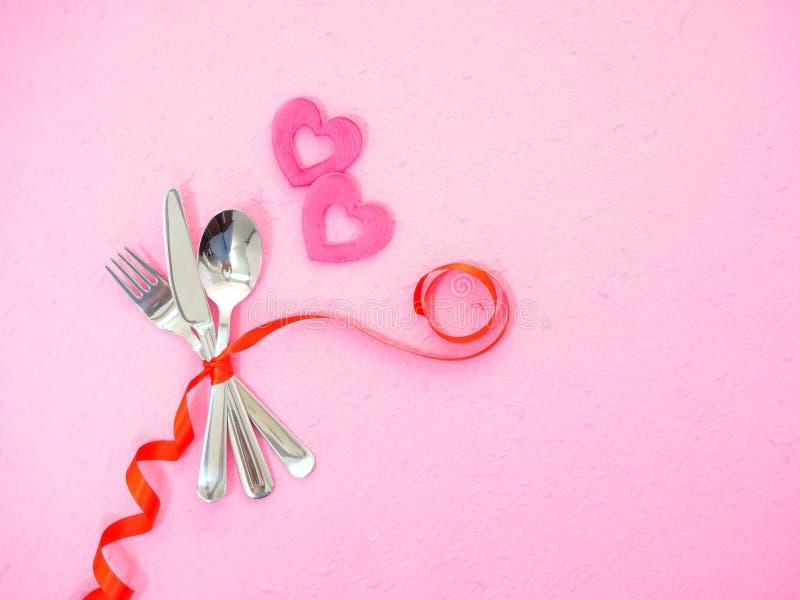 cubiertos y corazones en la tabla rosada fotografía de archivo
