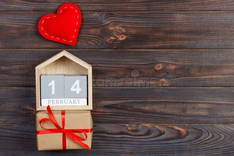 Cubique el calendario con la caja roja del corazón y de regalo en la tabla de madera con el espacio de la copia 14 de febrero con fotos de archivo