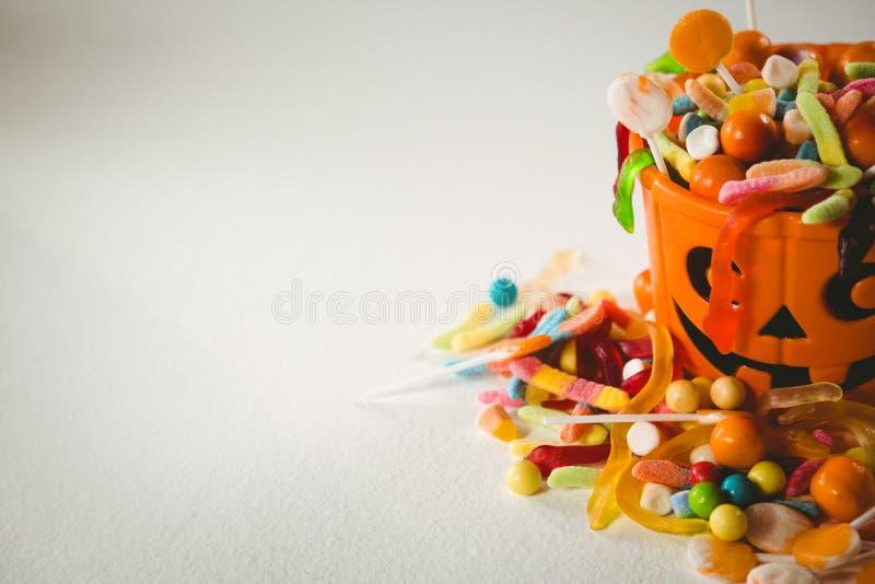 Cubo anaranjado con la diversa comida dulce durante Halloween en el fondo blanco fotos de archivo