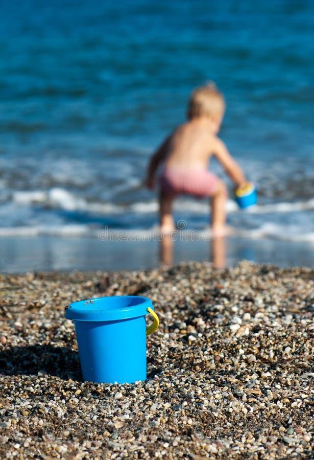 Cubo azul en la playa con imagen de archivo