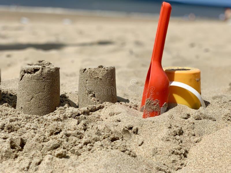 cubo con la cucharada para construir castillos de arena en la playa en un día de verano imagen de archivo libre de regalías