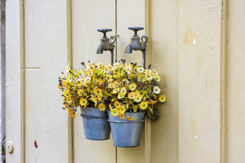 Cubo con las flores amarillas que cuelgan en un grifo viejo del metal imagen de archivo libre de regalías