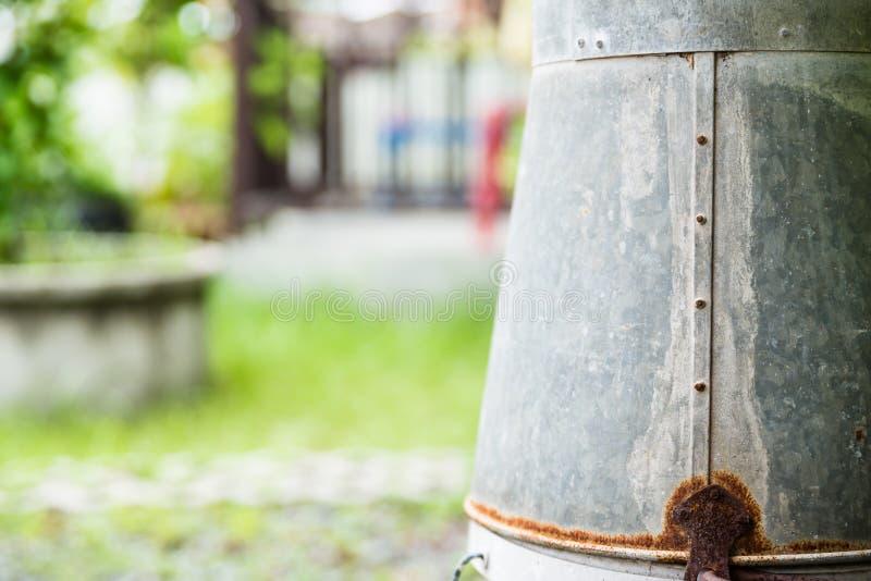 Cubo de agua aherrumbrado del cinc en jardín imágenes de archivo libres de regalías