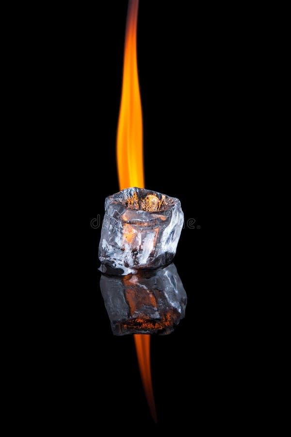 Cubo de gelo com a chama na superfície brilhante do preto imagem de stock
