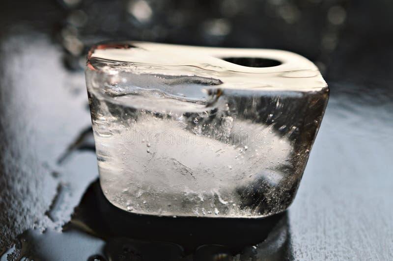 Cubo de gelo que derrete sob a madeira preta imagem de stock