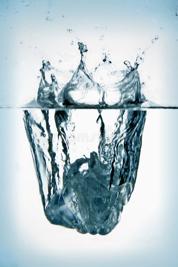 Cubo de gelo que espirra na água. foto de stock royalty free