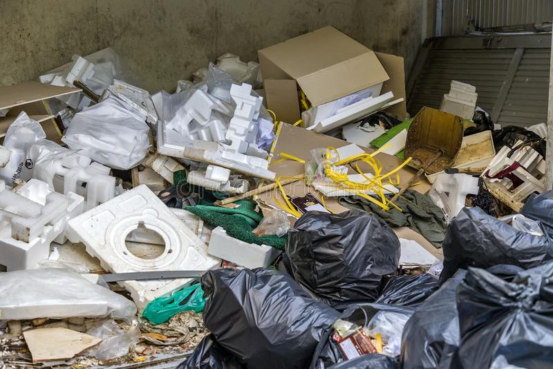 Cubo de la basura con la espuma, cajón de papel, bolso de basura negro, zapatos viejos fotografía de archivo