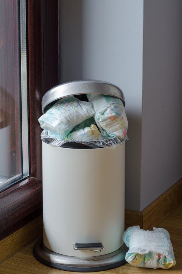 Cubo de la basura por completo de pañales sucios usados foto de archivo