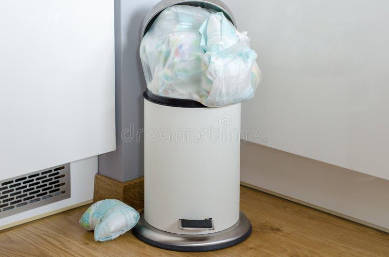 Cubo de la basura por completo de pañales sucios usados imagen de archivo