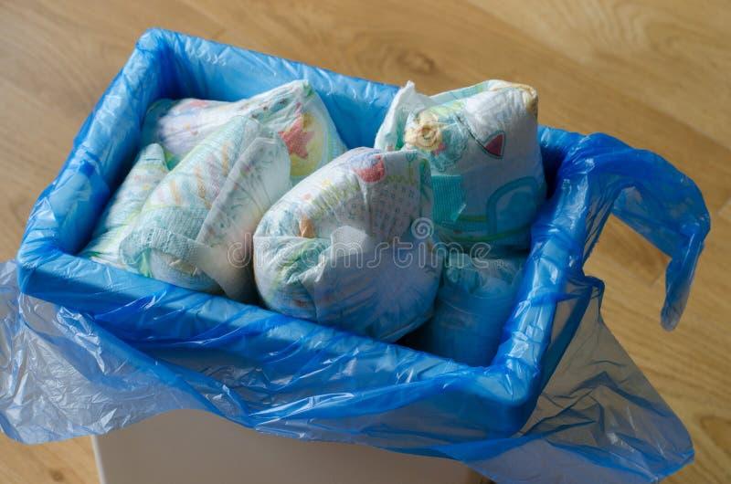 Cubo de la basura por completo de pañales usados foto de archivo