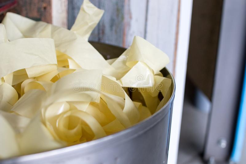 Cubo de la basura por completo de tiras de papel en una escuela Los niños reciclan la parte imagen de archivo