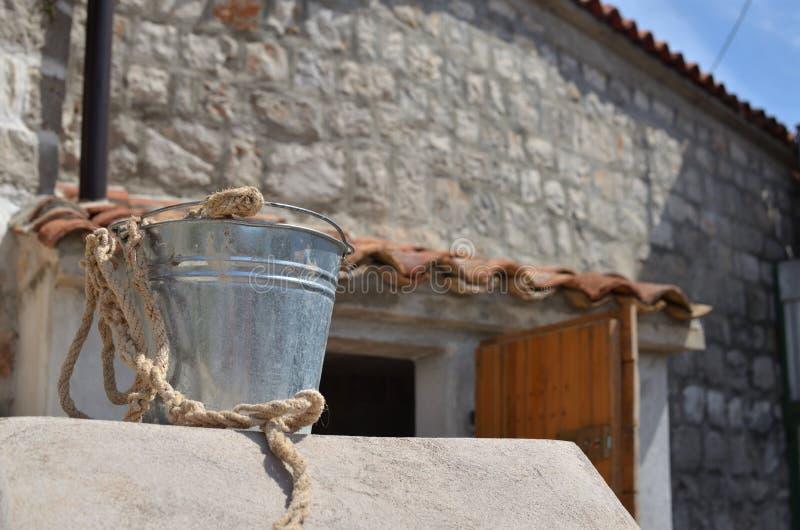 Cubo de la lata y casa del pueblo fotografía de archivo libre de regalías