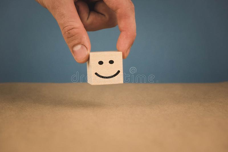 Cubo de madeira e a imagem de um smiley de sorriso que seja a m?o dos in person fotos de stock