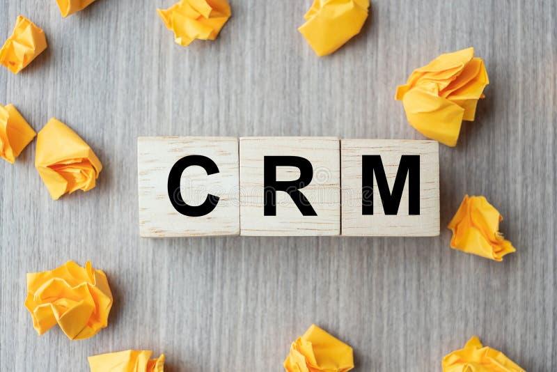Cubo de madera con la gestión de la relación del cliente del texto de CRM y documento desmenuzado sobre fondo de la tabla Financi imagen de archivo libre de regalías