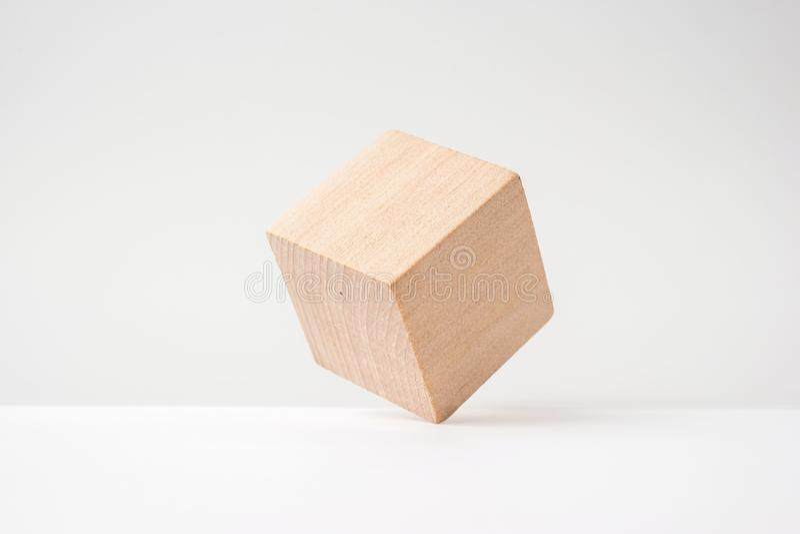 Cubo de madera real geométrico abstracto con la disposición surrealista en el fondo blanco fotos de archivo