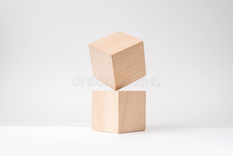 Cubo de madera real geométrico abstracto con la disposición surrealista en el fondo blanco imagen de archivo