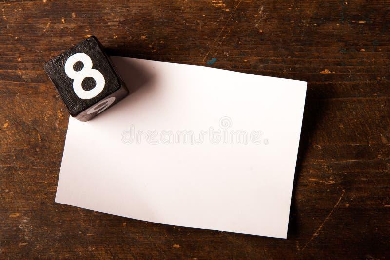 Cubo de papel e de madeira com número na tabela de madeira, 8 foto de stock royalty free