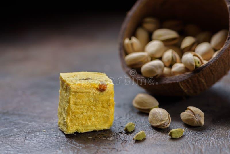 Cubo de postre papdi soan, granos cardamomo, pistachos y almendros en la superficie de la cocina de hormigón imágenes de archivo libres de regalías