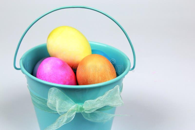 Cubo decorativo azul del metal que lleva a cabo el isolat colorido de los huevos de Pascua imagen de archivo