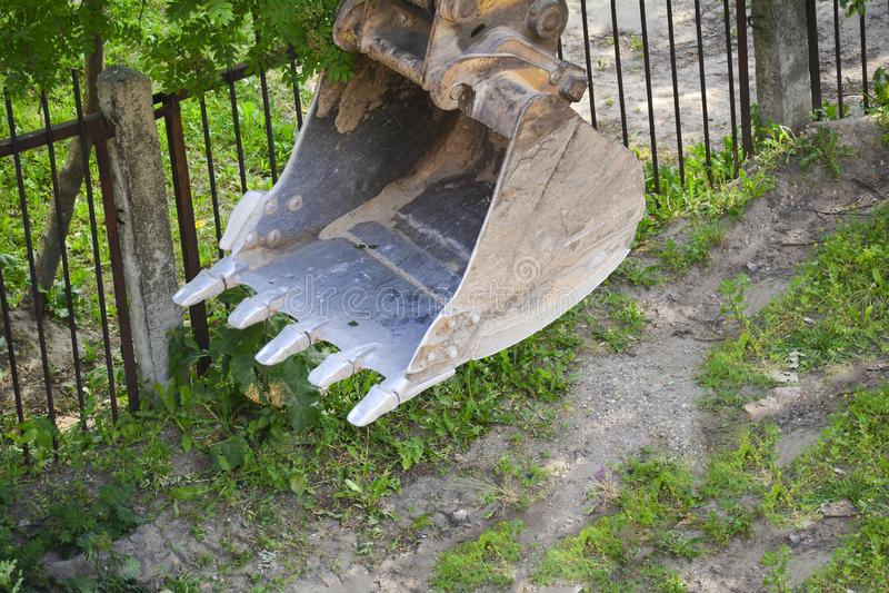 Cubo del excavador en el emplazamiento de la obra Ciérrese para arriba del cubo del metal de un excavador Maquinaria pesada en el fotos de archivo libres de regalías
