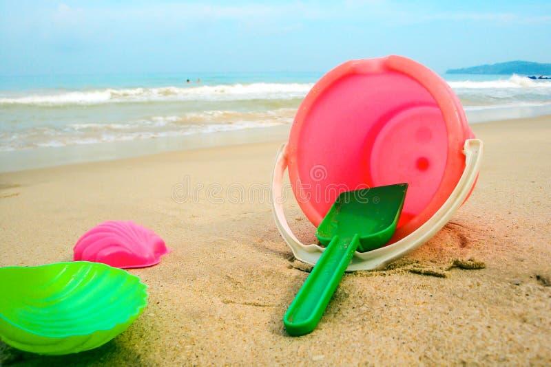 Cubo del ` s de los niños y moldes coloreados en la playa en la arena fotografía de archivo