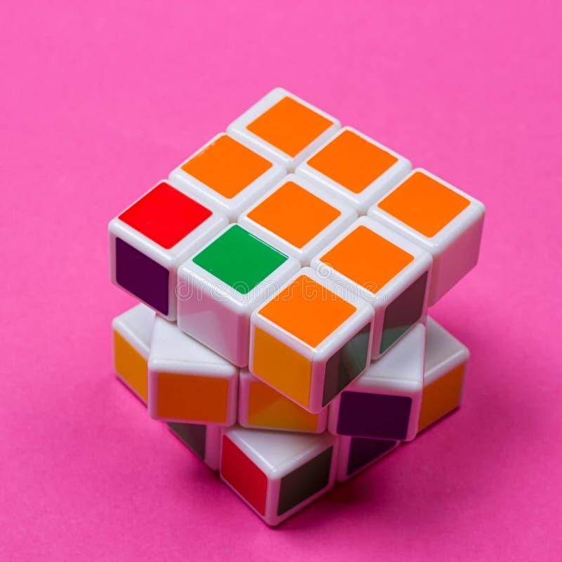 Cubo del ` s de Rubik en el rosa imagen de archivo