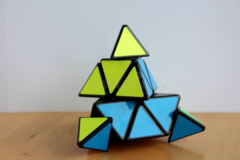 Cubo del ` s Pyraminx de Rubik en una tabla fotos de archivo libres de regalías