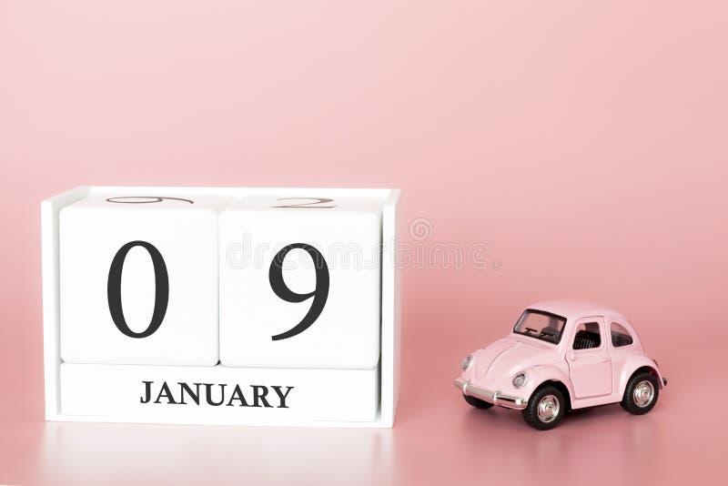 Cubo di legno del primo piano il nono gennaio Giorno 9 del mese di gennaio, calendario su un fondo rosa immagini stock