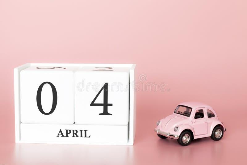 Cubo di legno del primo piano il quarto aprile Giorno 4 del mese di aprile, calendario su un fondo rosa con fotografia stock