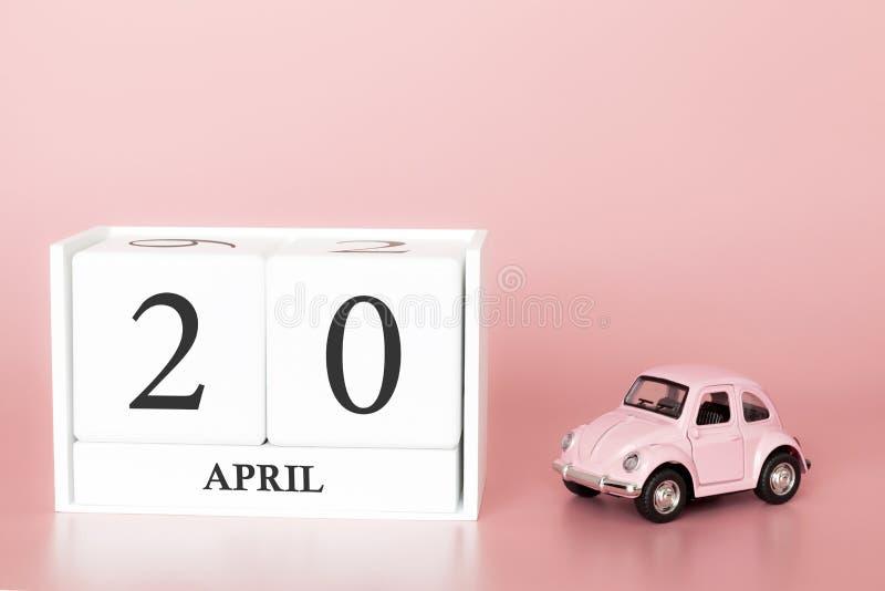 Cubo di legno del primo piano il ventesimo aprile Giorno 20 del mese di aprile, calendario su un fondo rosa fotografia stock