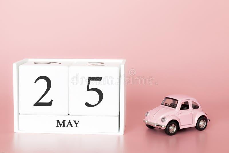 Cubo di legno del primo piano venticinquesimo maggio Il giorno 25 di pu? mese, calendario su un fondo rosa con fotografia stock