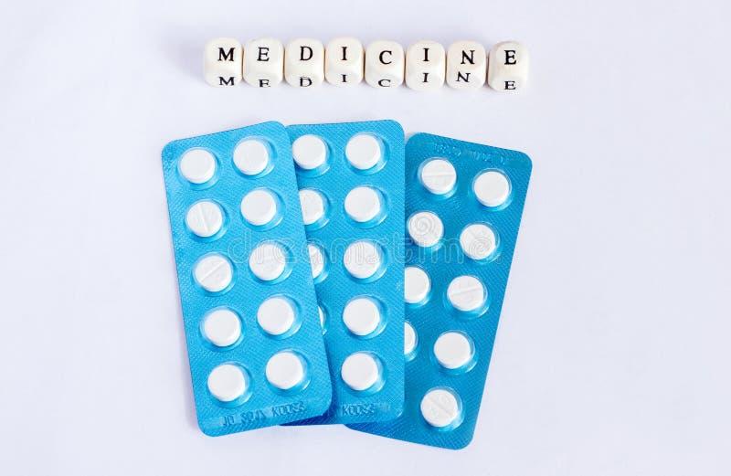 """Cubo di legno scritto """"della medicina """"con le pillole in bolla blu fotografia stock libera da diritti"""