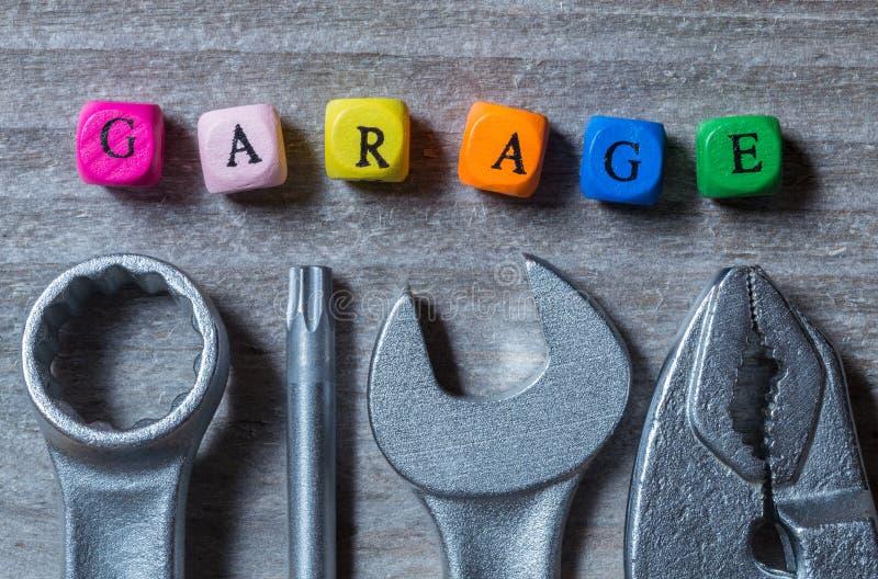 Cubo e ferramenta da letra da garagem no visualização de madeira cinzento fotos de stock