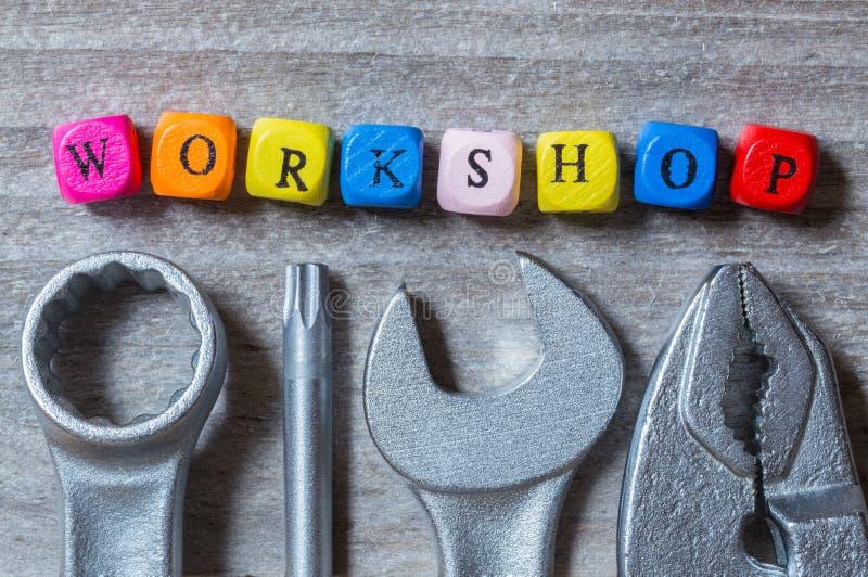 Cubo e ferramenta da letra da oficina no visualização de madeira cinzento foto de stock