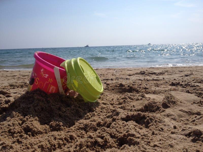 Cubo en una playa foto de archivo