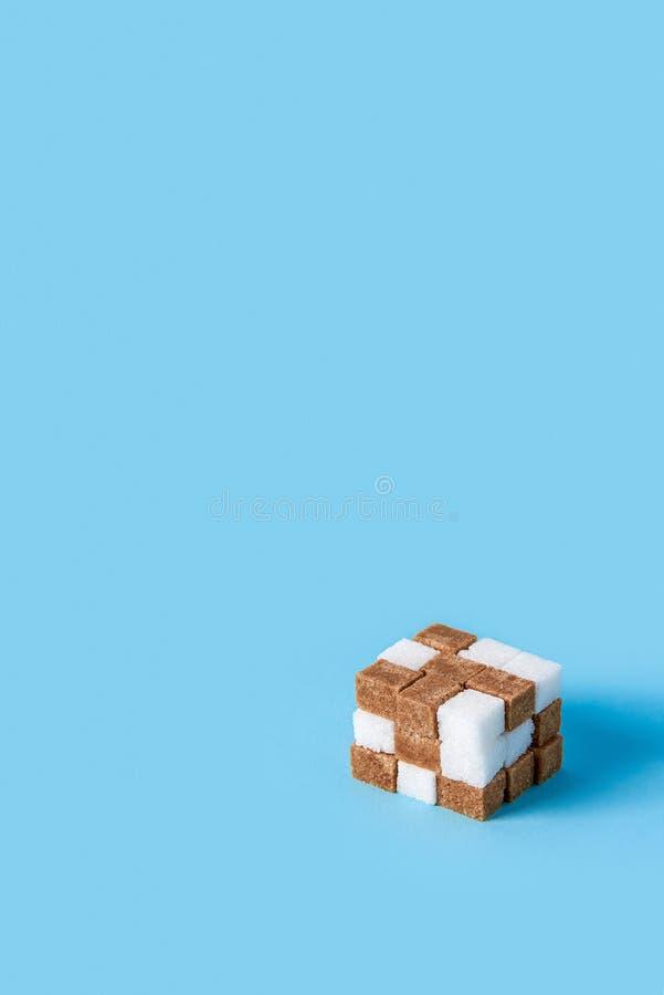 Cubo hecho de los cubos del azúcar blanco y marrón aislados en fondo azul imagen de archivo libre de regalías