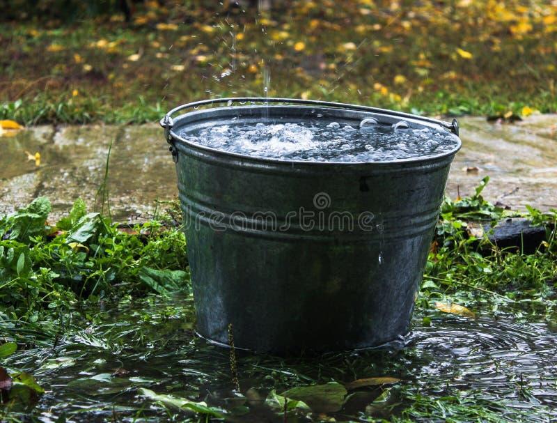 Cubo lleno de agua Lluvia goteo del tejado fotografía de archivo libre de regalías