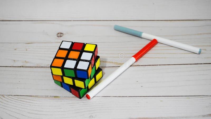 Cubo mágico, cubo de Rubik, e lápis no fundo de madeira da tabela enigma da combinação 3D imagem de stock