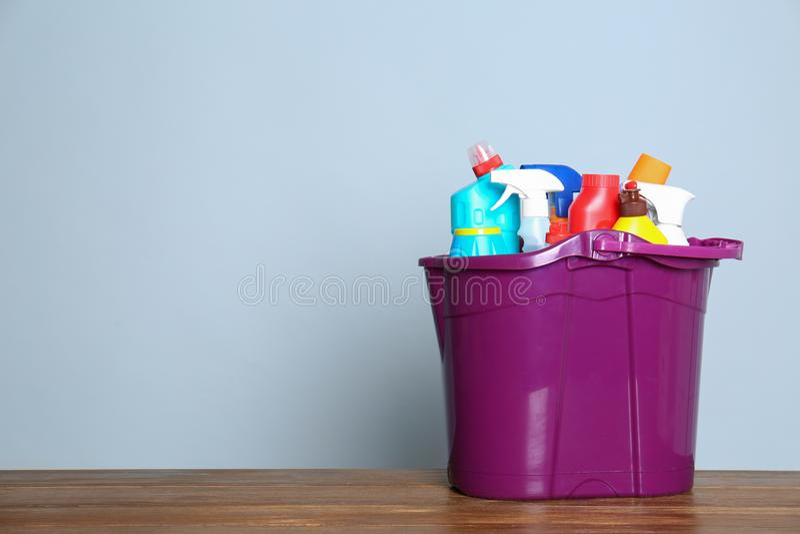 Cubo plástico con diversos productos de limpieza en la tabla contra fondo del color foto de archivo