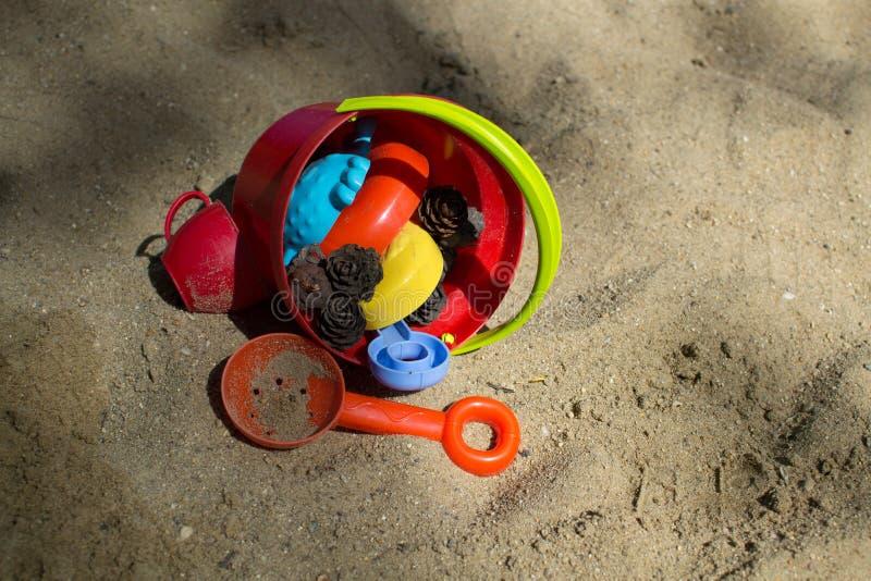 Cubo rojo con los juguetes de los niños en la arena fotos de archivo