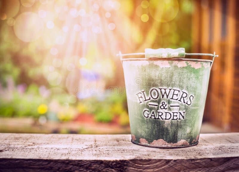 Cubo vacío en la tabla de madera vieja sobre fondo del jardín del verano o del otoño fotografía de archivo