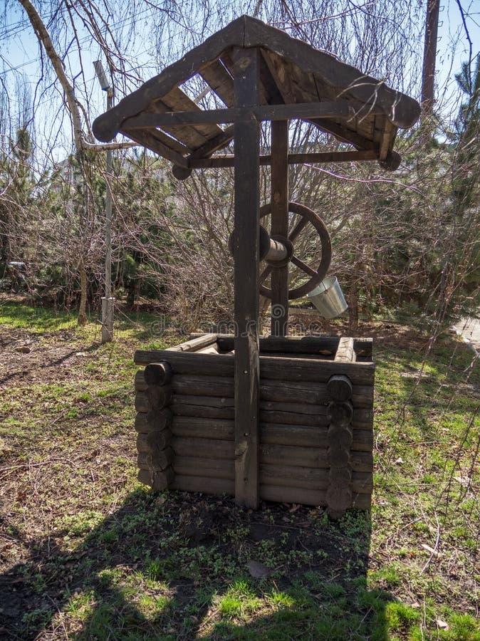 Cubo viejo de la yarda del pozo del día de primavera de la rama de árboles del parque de la ciudad para beber la barra de madera  fotos de archivo libres de regalías