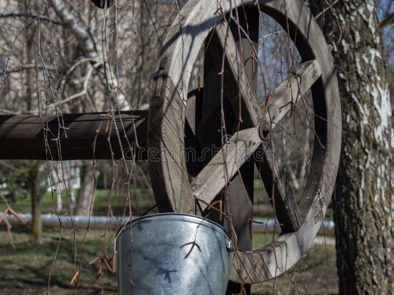 Cubo viejo de la yarda del pozo del día de primavera de la rama de árboles del parque de la ciudad para beber la barra de madera  foto de archivo