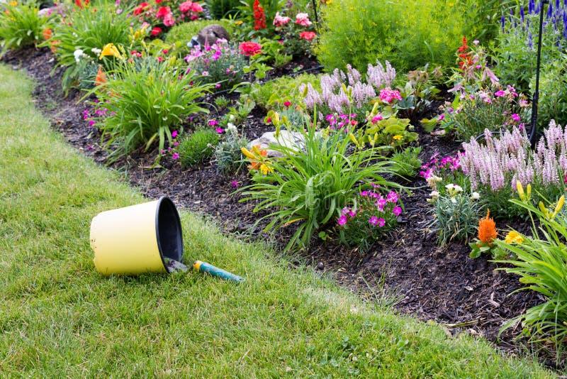 Cubo volcado que contiene los utensilios de jardinería foto de archivo