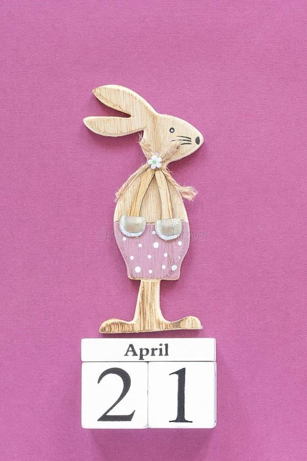 Cubos calendário o 21 de abril e coelhinho da Páscoa de madeira no fundo de papel roxo Molde católico da Páscoa do conceito para  fotos de stock royalty free