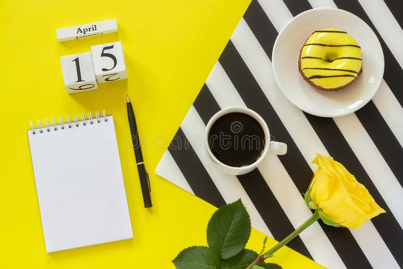 Cubos calendario 15 de abril de madera Taza de café, de buñuelo amarillo y de rosa en la servilleta blanco y negro, libreta abier foto de archivo libre de regalías