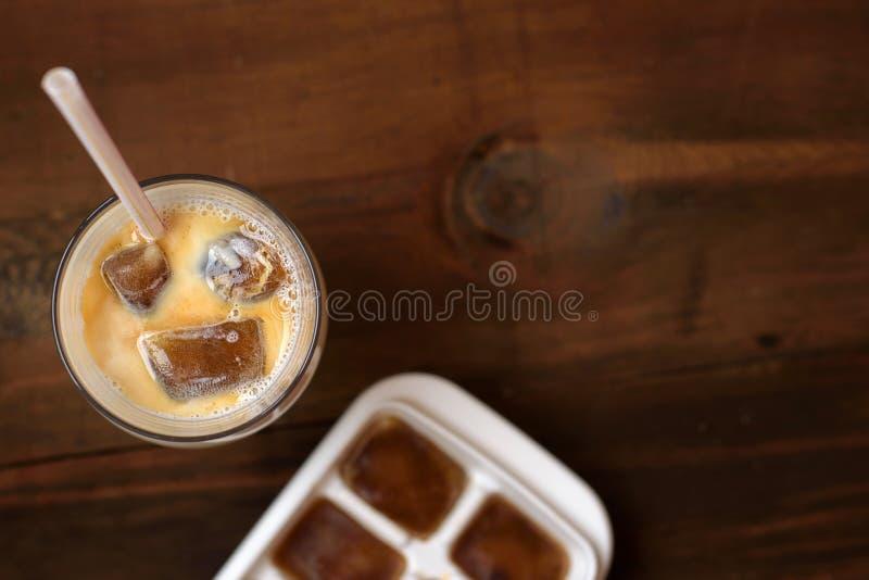 Cubos congelados com leite - cocktail do café na tabela de madeira escura Vista superior foto de stock royalty free
